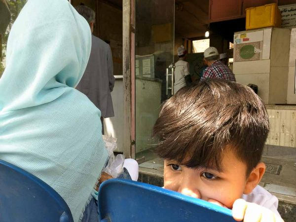 Child And Mother Waiting At Nanvaii (breadmaking Shop) In Central Mashhad, Iran
